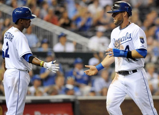 Aug 21, 2013; Kansas City, MO, USA; Kansas City Royals left fielder Alex Gordon (4) is congratulated by shortstop Alcides Escobar (2) after scoring in the sixth inning of the game against the Chicago White Sox at Kauffman Stadium. Chicago won 5-2. Mandatory Credit: Denny Medley-USA TODAY Sports
