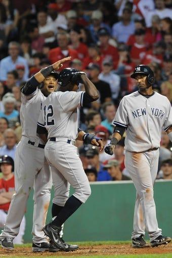 Aug 16, 2013; Boston, MA, USA; New York Yankees second baseman Robinson Cano (24) congratulates left fielder Alfonso Soriano (12) after hitting a three run home run during the third inning against the Boston Red Sox at Fenway Park. Mandatory Credit: Bob DeChiara-USA TODAY Sports