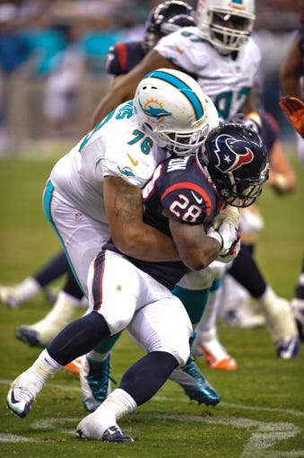 Aug 17, 2013; Houston, TX, USA; Miami Dolphins defensive tackle A.J. Francis (76) tackles Houston Texans running back Dennis Johnson (28) during the game at Reliant Stadium. The Texans defeated the Dolphins 24-17. Mandatory Credit: Jerome Miron-USA TODAY Sports
