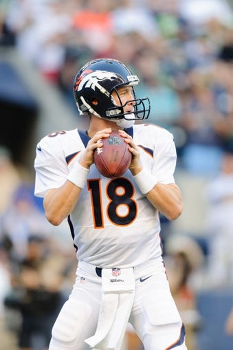 Aug 17, 2013; Seattle, WA, USA; Denver Broncos quarterback Peyton Manning (18) looks for an open receiver during the game against the Seattle Seahawks at CenturyLink Field. Seattle defeated Denver 40-10. Mandatory Credit: Steven Bisig-USA TODAY Sports