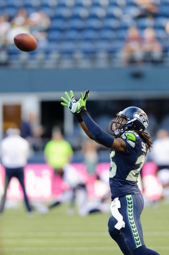 Aug 17, 2013; Seattle, WA, USA; Seattle Seahawks cornerback Richard Sherman (25) catches a pass during team warm ups prior to the game against the Denver Broncos at CenturyLink Field. Seattle defeated Denver 40-10. Mandatory Credit: Steven Bisig-USA TODAY Sports