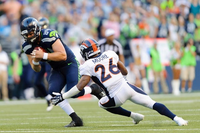 Aug 17, 2013; Seattle, WA, USA; Seattle Seahawks tight end Sean McGrath (84) runs past Denver Broncos free safety Rahim Moore (26) after receiving a pass during the 1st half at CenturyLink Field. Seattle defeated Denver 40-10. Mandatory Credit: Steven Bisig-USA TODAY Sports