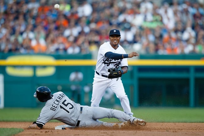 Aug 3, 2013; Detroit, MI, USA; Detroit Tigers second baseman Ramon Santiago (39) makes a throw to first as Chicago White Sox second baseman Gordon Beckham (15) slides into second base in the third inning at Comerica Park. Mandatory Credit: Rick Osentoski-USA TODAY Sports