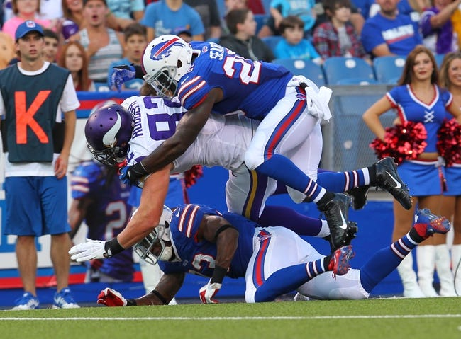 Aug 16, 2013; Orchard Park, NY, USA;  Buffalo Bills strong safety Da'Norris Searcy (25) tackles Minnesota Vikings tight end Kyle Rudolph (82) at Ralph Wilson Stadium.  Mandatory Credit: Timothy T. Ludwig-USA TODAY Sports