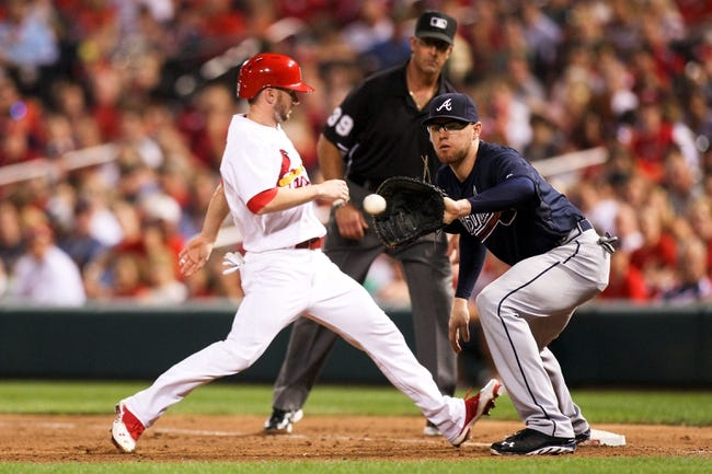 Aug 22, 2013; St. Louis, MO, USA; St. Louis Cardinals center fielder Shane Robinson (43) steps back to first base to avoid a pickoff throw to Atlanta Braves first baseman Freddie Freeman (5) in the sixth inning at Busch Stadium. Mandatory Credit: Scott Kane-USA TODAY Sports
