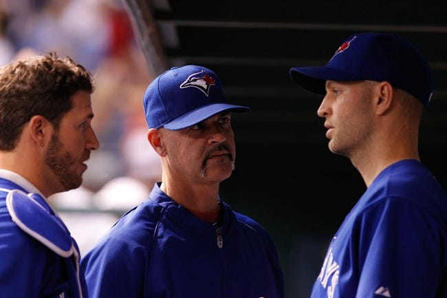 Aug 17, 2013; St. Petersburg, FL, USA; Toronto Blue Jays pitching coach Pete Walker (40) talks with starting pitcher J.A. Happ (48) and catcher J.P. Arencibia (9) in the dugout against the Tampa Bay Rays at Tropicana Field. Toronto Blue Jays defeated the Tampa Bay Rays 6-2. Mandatory Credit: Kim Klement-USA TODAY Sports