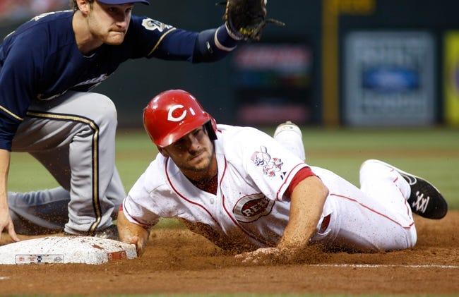 Aug 24, 2013; Cincinnati, OH, USA; Cincinnati Reds left fielder Chris Heisey, right, reaches safely back to first beating the tag from Milwaukee Brewers first baseman Jonathan Lucroy (20), left, in the third inning at Great American Ball Park. Mandatory Credit: David Kohl-USA TODAY Sports