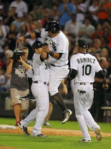 Aug 24, 2013; Chicago, IL, USA; Chicago White Sox catcher Josh Phegley (left) is congratulated for hitting a game winning RBI single by  center fielder Alejandro De Aza (center) and shortstop Alexei Ramirez (right) during the ninth inning against the Texas Rangers at US Cellular Field. Chicago won 3-2. Mandatory Credit: Dennis Wierzbicki-USA TODAY Sports