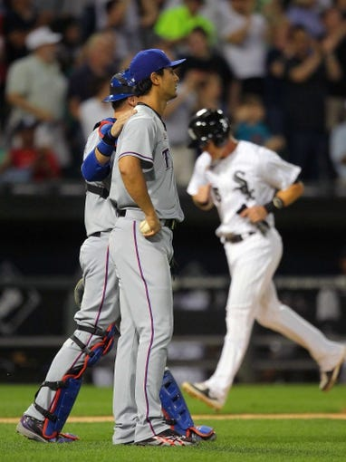 Aug 24, 2013; Chicago, IL, USA; Texas Rangers catcher A.J. Pierzynski (left) meets with Yu Darvish (right) while Chicago White Sox second baseman Gordon Beckham (background) approaches home plate during the sixth inning at US Cellular Field. Chicago won 3-2. Mandatory Credit: Dennis Wierzbicki-USA TODAY Sports