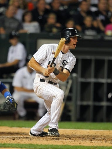 Aug 24, 2013; Chicago, IL, USA; Chicago White Sox third baseman Conor Gillaspie (12) hits a single during the seventh inning against the Texas Rangers at US Cellular Field. Chicago won 3-2. Mandatory Credit: Dennis Wierzbicki-USA TODAY Sports