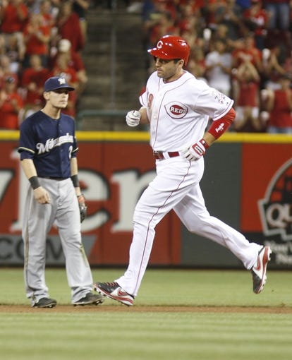 Aug 24, 2013; Cincinnati, OH, USA; Cincinnati Reds first baseman Joey Votto (19) rounds the bases past Milwaukee Brewers second baseman Scooter Gennett (2) after Votto hit a solo home run off Milwaukee Brewers relief pitcher Mike Gonzalez (not pictured) in the seventh inning at Great American Ball Park. The Reds defeated the Brewers 6-3.Mandatory Credit: David Kohl-USA TODAY Sports