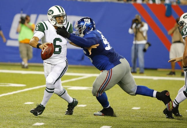 Aug 24, 2013; East Rutherford, NJ, USA; New York Giants defensive tackle Marvin Austin (96) sacks New York Jets quarterback Mark Sanchez (6) during the second half at MetLife Stadium. New York Jets defeat the New York Giants 24-21 in OT. Mandatory Credit: Jim O'Connor-USA TODAY Sports