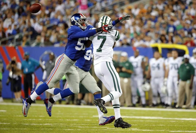 Aug 24, 2013; East Rutherford, NJ, USA; New York Jets quarterback Geno Smith (7) just gets ball away before New York Giants linebacker Jacquian Williams (57) wraps him up during the first half at MetLife Stadium. Mandatory Credit: Jim O'Connor-USA TODAY Sports