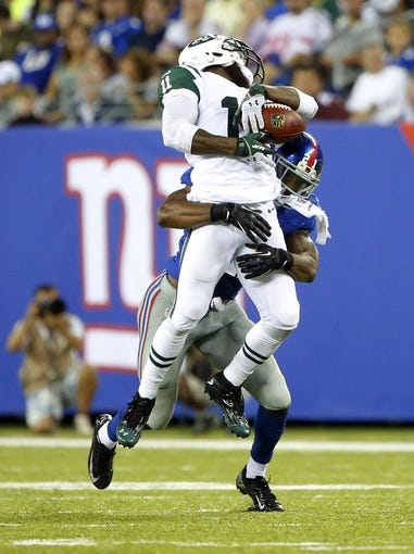Aug 24, 2013; East Rutherford, NJ, USA; New York Giants safety Ryan Mundy (21) puts a big hit on New York Jets wide receiver Jeremy Kerley (11) and dislodges the ball during the first half at MetLife Stadium. Mandatory Credit: Jim O'Connor-USA TODAY Sports