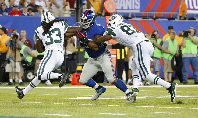 Aug 24, 2013; East Rutherford, NJ, USA; New York Jets running back Chris Ivory (33) runs into New York Giants defensive end Justin Tuck (91) during the first half at MetLife Stadium. Mandatory Credit: Jim O'Connor-USA TODAY Sports