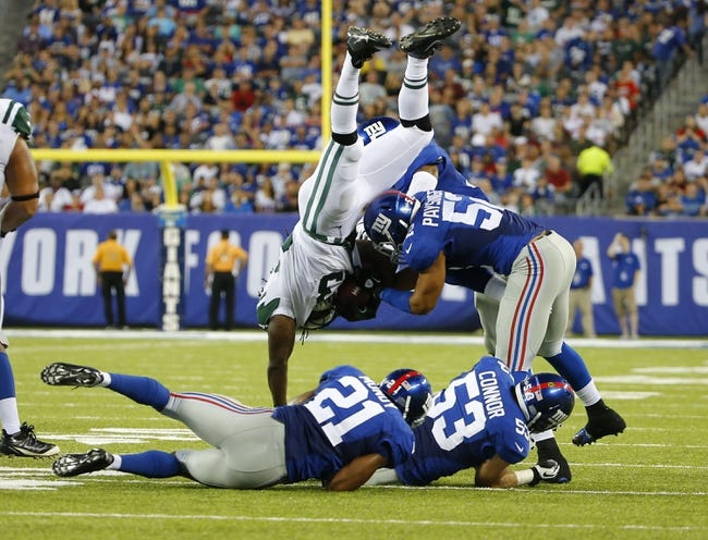 Aug 24, 2013; East Rutherford, NJ, USA; New York Giants linebacker Spencer Paysinger (52) upends New York Giants running back Da'Rel Scott (33) during the first half at MetLife Stadium. Mandatory Credit: Jim O'Connor-USA TODAY Sports