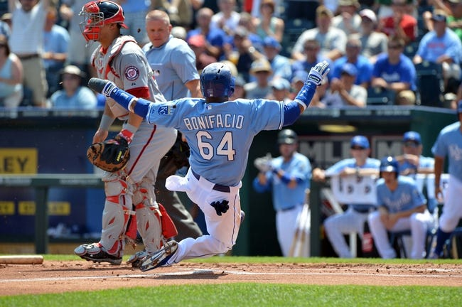 Aug 25, 2013; Kansas City, MO, USA; Kansas City Royals second basemen Emilio Bonifacio (64) scores as he slides home past Washington Nationals catcher Wilson Ramos (40) during the first inning at Kauffman Stadium.  Mandatory Credit: Peter G. Aiken-USA TODAY Sports