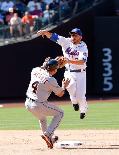 Aug 25, 2013; New York, NY, USA;  New York Mets shortstop Omar Quintanilla (3) turns a double play over Detroit Tigers second baseman Omar Infante (4) during the sixth inning at Citi Field. Mandatory Credit: Anthony Gruppuso-USA TODAY Sports