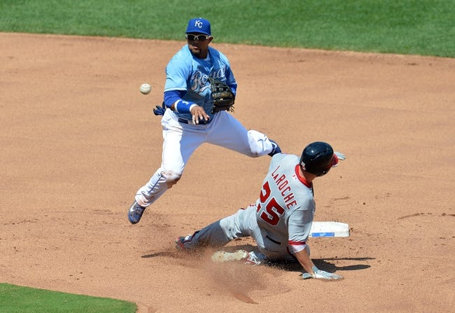 Aug 25, 2013; Kansas City, MO, USA; Kansas City Royals second basemen Emioio Bonifacio (64) turns a double play over Washington Nationals base runner Adam Laroche (25) during the fourth inning at Kauffman Stadium.  Mandatory Credit: Peter G. Aiken-USA TODAY Sports