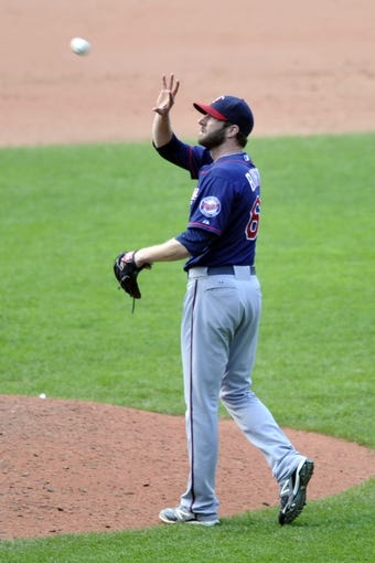 Aug 25, 2013; Cleveland, OH, USA; Minnesota Twins relief pitcher Jared Burton (61) catches a new baseball after giving up a home run in the eighth inning against the Cleveland Indians at Progressive Field. Mandatory Credit: David Richard-USA TODAY Sports