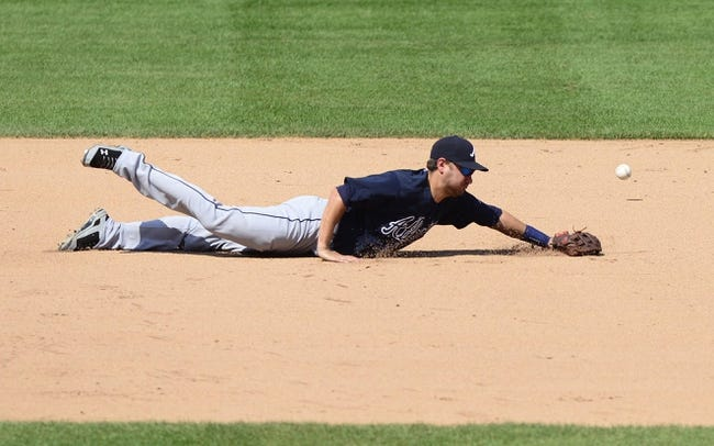 Aug 25, 2013; St. Louis, MO, USA; Atlanta Braves third baseman Paul Janish (4) dives unsuccessfully for a ball hit by St. Louis Cardinals first baseman Allen Craig (not pictured) during the sixth inning at Busch Stadium. Atlanta defeated St. Louis 5-2. Mandatory Credit: Jeff Curry-USA TODAY Sports