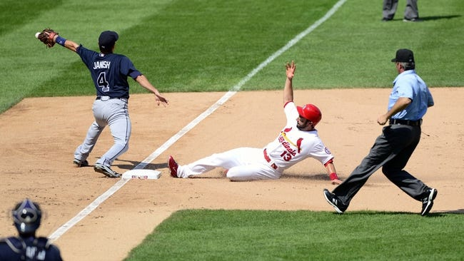Aug 25, 2013; St. Louis, MO, USA; St. Louis Cardinals second baseman Matt Carpenter (13) slides safely into third as Atlanta Braves third baseman Paul Janish (4) tries to handle the throw during the sixth inning at Busch Stadium. Atlanta defeated St. Louis 5-2. Mandatory Credit: Jeff Curry-USA TODAY Sports