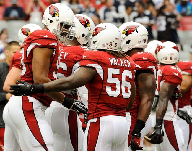 Aug 17, 2013; Phoenix, AZ, USA; Arizona Cardinals defensive end Calais Campbell (93) and inside linebacker Reggie Walker (56) greet each other during warm ups before the first quarter against the Dallas Cowboys at University of Phoenix Stadium. The Cardinals defeated the Cowboys 12-7. Mandatory Credit: Casey Sapio-USA TODAY Sports