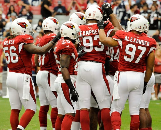 Aug 17, 2013; Phoenix, AZ, USA; Arizona Cardinals inside linebacker Reggie Walker (56) cornerback Jerraud Powers (25) defensive end Calais Campbell (93) and outside linebacker Lorenzo Alexander (97) huddle up during warm ups before the first quarter against the Dallas Cowboys at University of Phoenix Stadium. The Cardinals defeated the Cowboys 12-7. Mandatory Credit: Casey Sapio-USA TODAY Sports