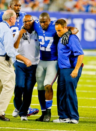 Aug 24, 2013; East Rutherford, NJ, USA; New York Giants safety Stevie Brown (27) is helped off field after injuring left knee during interception return against the New York Jets at MetLife Stadium. Mandatory Credit: Jim O'Connor-USA TODAY Sports