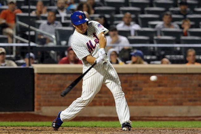 Aug 26, 2013; New York, NY, USA; New York Mets catcher Travis d'Arnaud (15) hits a single against the Philadelphia Phillies during the eighth inning of a game at Citi Field. The Phillies defeated the Mets 2-1. Mandatory Credit: Brad Penner-USA TODAY Sports