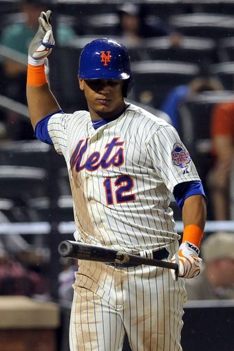 Aug 26, 2013; New York, NY, USA; New York Mets center fielder Juan Lagares (12) reacts after striking out against the Philadelphia Phillies during the eighth inning of a game at Citi Field. The Phillies defeated the Mets 2-1. Mandatory Credit: Brad Penner-USA TODAY Sports