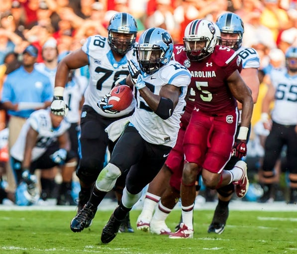 Aug 29, 2013; Columbia, SC, USA; North Carolina Tar Heels running back A.J. Blue (15) runs for yardage as South Carolina Gamecocks defensive end Darius English (5) pursues in the second quarter at Williams-Brice Stadium. Mandatory Credit: Jeff Blake-USA TODAY Sports