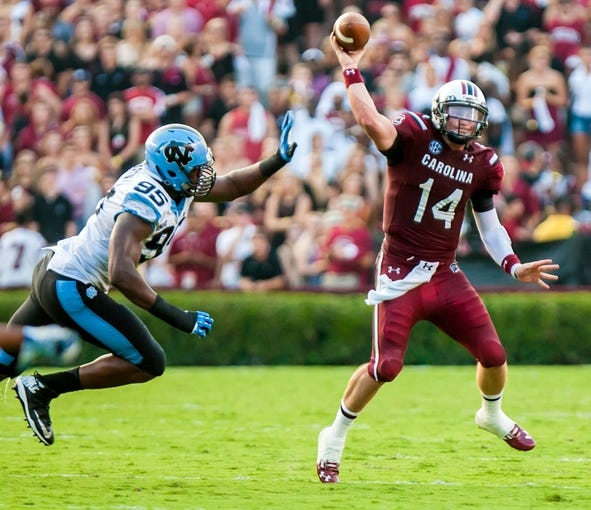Aug 29, 2013; Columbia, SC, USA; South Carolina Gamecocks quarterback Connor Shaw (14) passes as he is pressured by North Carolina Tar Heels defensive end Kareem Martin (95) in the second quarter at Williams-Brice Stadium. Mandatory Credit: Jeff Blake-USA TODAY Sports