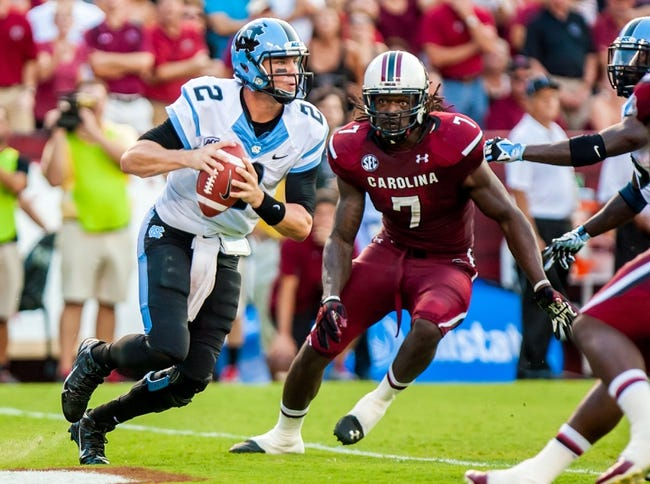 Aug 29, 2013; Columbia, SC, USA; North Carolina Tar Heels quarterback Bryn Renner (2) scrambles as he is pursued by South Carolina Gamecocks defensive end Jadeveon Clowney (7) in the second quarter at Williams-Brice Stadium. Mandatory Credit: Jeff Blake-USA TODAY Sports
