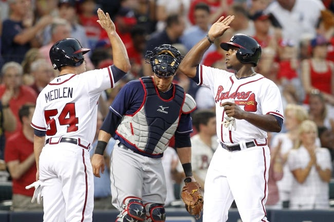 Aug 29, 2013; Atlanta, GA, USA; Atlanta Braves starting pitcher Kris Medlen (54) and left fielder Justin Upton (8) celebrate after scoring against the Cleveland Indians in the third inning at Turner Field. Mandatory Credit: Brett Davis-USA TODAY Sports