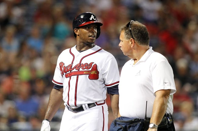 Aug 29, 2013; Atlanta, GA, USA; Atlanta Braves left fielder Justin Upton (8) talks to assistant athletic trainer Jim Lovell after being hit by a pitch against the Cleveland Indians in the fifth inning at Turner Field. Mandatory Credit: Brett Davis-USA TODAY Sports