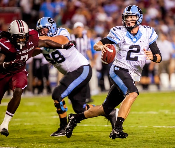 Aug 29, 2013; Columbia, SC, USA; North Carolina Tar Heels quarterback Bryn Renner (2) scrambles for yardage as South Carolina Gamecocks defensive end Jadeveon Clowney (7) pursues in the third quarter at Williams-Brice Stadium. Mandatory Credit: Jeff Blake-USA TODAY Sports