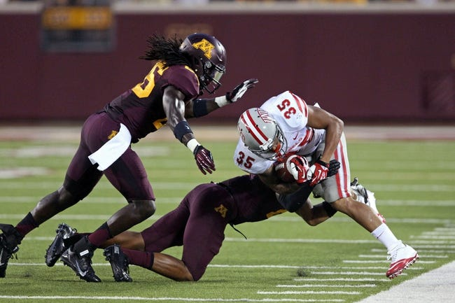 Aug 29, 2013; Minneapolis, MN, USA; UNLV Rebels running back Tim Cornett (35) gets a first down as he gets tackled by Minnesota Golden Gophers defensive back Cedric Thompson (2) and linebacker De'Vondre Campbell (26) in the third quarter at TCF Bank Stadium. The Gophers won 51-23. Mandatory Credit: Jesse Johnson-USA TODAY Sports