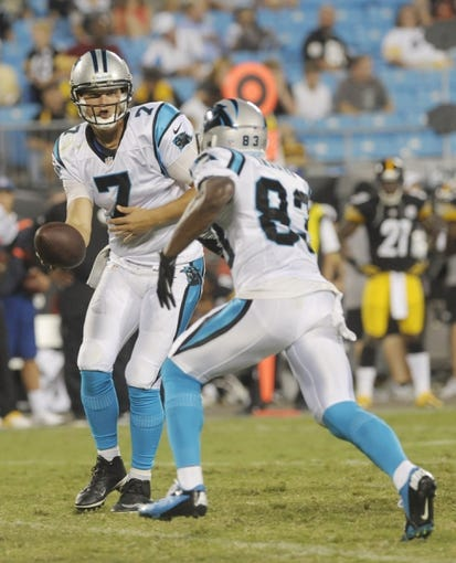 Aug 29, 2013; Charlotte, NC, USA; Carolina Panthers quarterback Jimmy Clausen (7) hands off to wide receiver Taulib Ikharo (83) during the game against the Pittsburgh Steelers at Bank Of America Stadium. Panthers win 25-10. Mandatory Credit: Sam Sharpe-USA TODAY Sports