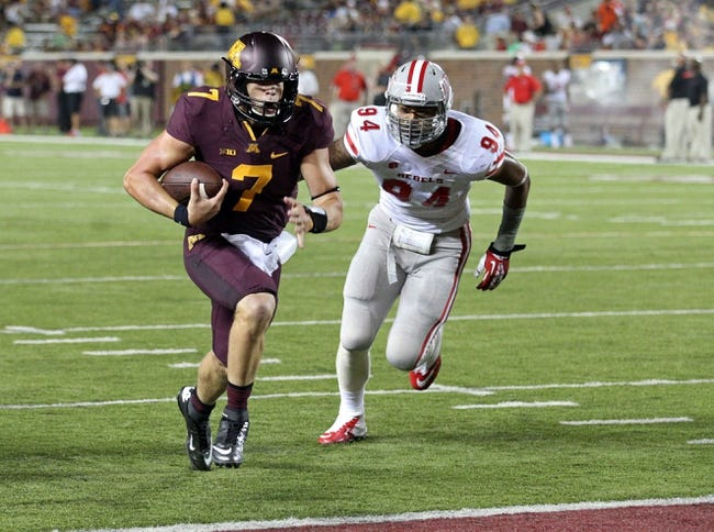 Aug 29, 2013; Minneapolis, MN, USA; Minnesota Golden Gophers quarterback Mitch Leidner (7) runs in for a touchdown past UNLV Rebels defensive lineman Jeremiah Valoaga (94) in the fourth quarter at TCF Bank Stadium. The Gophers won 51-23. Mandatory Credit: Jesse Johnson-USA TODAY Sports