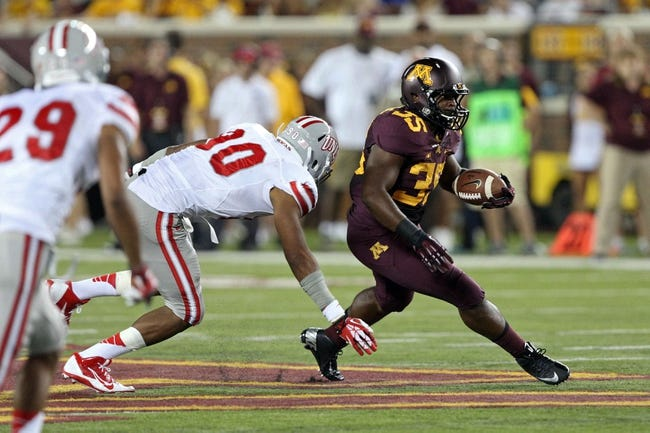 Aug 29, 2013; Minneapolis, MN, USA; Minnesota Golden Gophers running back Rodrick Williams Jr. (35) runs past UNLV Rebels defensive lineman Parker Holloway (90) for a first down in the third quarter at TCF Bank Stadium. The Gophers won 51-23. Mandatory Credit: Jesse Johnson-USA TODAY Sports