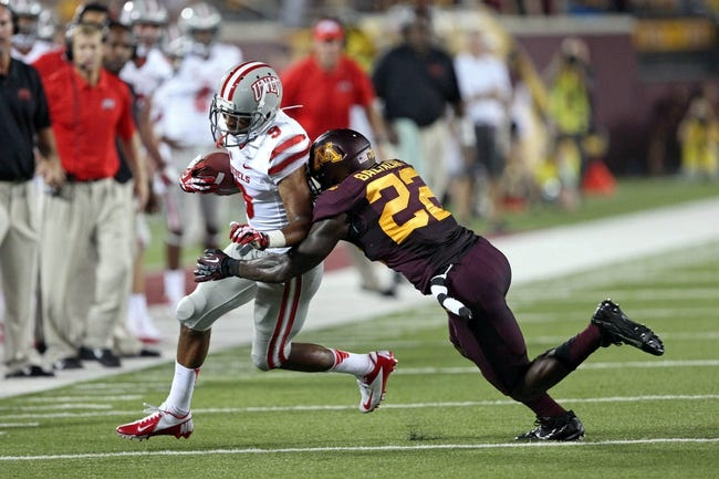 Aug 29, 2013; Minneapolis, MN, USA; Minnesota Golden Gophers wide receiver Jeff Borchardt (22) tackles UNLV Rebels wide receiver Aaron Criswell (9) after catching a pass in the third quarter at TCF Bank Stadium. The Gophers won 51-23. Mandatory Credit: Jesse Johnson-USA TODAY Sports