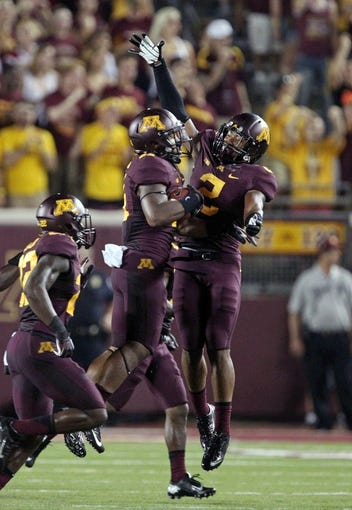 Aug 29, 2013; Minneapolis, MN, USA; Minnesota Golden Gophers defensive back Antonio Johnson (11) celebrates with defensive back Cedric Thompson (2) after intercepting a pass in the third quarter against the UNLV Rebels at TCF Bank Stadium. The Gophers won 51-23. Mandatory Credit: Jesse Johnson-USA TODAY Sports