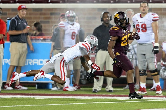 Aug 29, 2013; Minneapolis, MN, USA; Minnesota Golden Gophers running back David Cobb (27) runs with the ball as UNLV Rebels defensive back Kenneth Penny (17) attempts to make a tackle in the fourth quarter at TCF Bank Stadium. The Gophers won 51-23. Mandatory Credit: Jesse Johnson-USA TODAY Sports