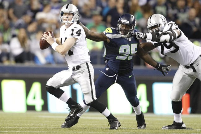 Aug 29, 2013; Seattle, WA, USA; Seattle Seahawks defensive end Benson Mayowa (95) beats a block by Oakland Raiders tackle Willie Smith (79) to force a fumble by quarterback Matthew McGloin (14) during the second half at CenturyLink Field. Mandatory Credit: Joe Nicholson-USA TODAY Sports