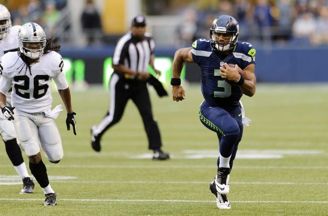 Aug 29, 2013; Seattle, WA, USA; Seattle Seahawks quarterback Russell Wilson (3) runs with the ball while being chased by Oakland Raiders free safety Usama Young (26) during the 1st half at CenturyLink Field. Seattle defeated Oakland 22-6. Mandatory Credit: Steven Bisig-USA TODAY Sports
