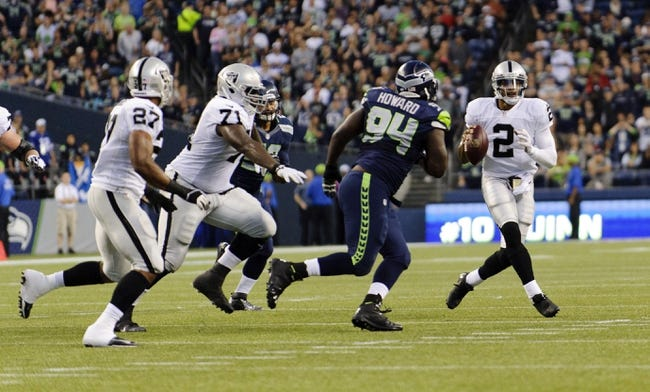 Aug 29, 2013; Seattle, WA, USA; Oakland Raiders quarterback Terrelle Pryor (2) looks to pass the ball while being guarded by Seattle Seahawks defensive tackle Jaye Howard (94) during the game at CenturyLink Field. Seattle defeated Oakland 22-6. Mandatory Credit: Steven Bisig-USA TODAY Sports