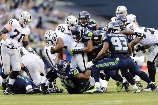 Aug 29, 2013; Seattle, WA, USA; Oakland Raiders running back Rashad Jennings (27) fights for extra yards while Seattle Seahawks middle linebacker Bobby Wagner (54) and outside linebacker K.J. Wright (50) attempt the tackle during the game at CenturyLink Field. Seattle defeated Oakland 22-6. Mandatory Credit: Steven Bisig-USA TODAY Sports