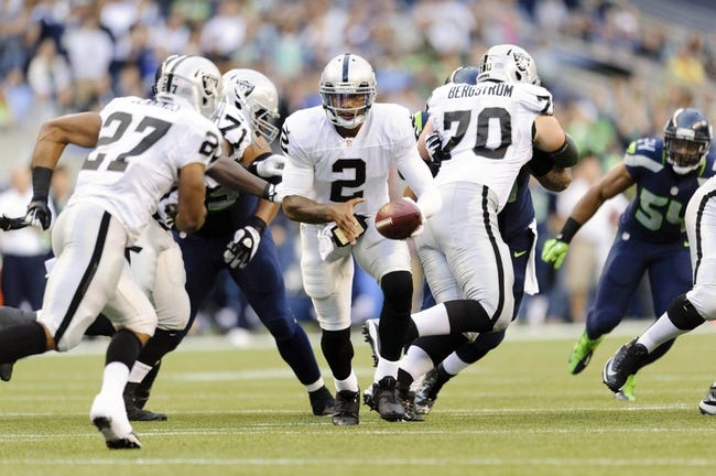 Aug 29, 2013; Seattle, WA, USA; Oakland Raiders quarterback Terrelle Pryor (2) hands the ball off to running back Rashad Jennings (27) during the 1st half against the Seattle Seahawks at CenturyLink Field. Seattle defeated Oakland 22-6. Mandatory Credit: Steven Bisig-USA TODAY Sports