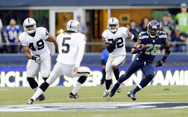 Aug 29, 2013; Seattle, WA, USA; Seattle Seahawks punt returner Walter Thurmond (28) returns a punt past Oakland Raiders punter Chris Kluwe (5) during the game at CenturyLink Field. Seattle defeated Oakland 22-6. Mandatory Credit: Steven Bisig-USA TODAY Sports